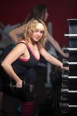 Girl trains biceps with dumbbells