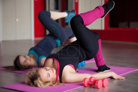 Photo pour Deux jolies filles font des exercices de fitness pour les hanches et les fesses, jambes balançoires en couché position sur tapis dans la salle de sport - image libre de droit