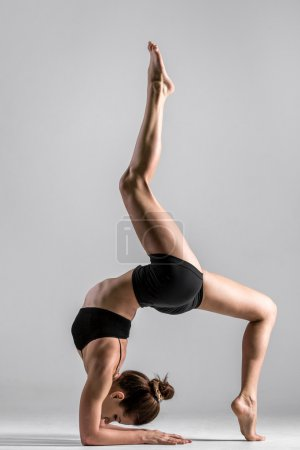 Photo for Beautiful sporty yogi girl practices yoga asana, handstand with bending, standing on forearms, standing on elbows - Royalty Free Image