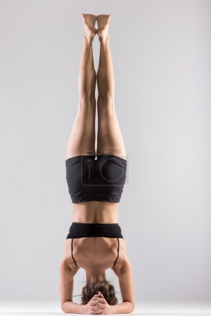 Photo pour Sporty girl doing Supported Headstand, yoga asana Sirsasana, Shirshasana, Sirshasana, Headstand on grey background, low key shot - image libre de droit