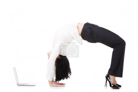 Photo for Attractive office employee, beautiful young female in formalwear standing in yoga position Chakrasana, Urdva Dhanurasana, Upward Bow (Wheel) Pose in front of laptop on white background, isolated, full length - Royalty Free Image