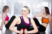 Krásná dívka dělá fitness cvičení s činkami ve třídě