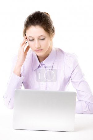 Tired young woman with bored look in front of laptop