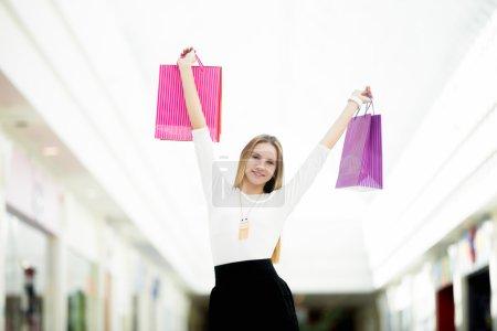 Photo pour Joyeux jeune femme heureuse de ses achats, dansant avec des sacs à provisions. Vente, escompte, mode, concepts d'offre rentable - image libre de droit