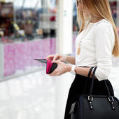 Young female in fashionable clothes looking into a wallet in sho