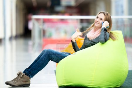 Smiling female sitting in bean bag in office or shopping center