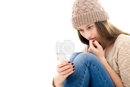Upset teenage girl looking at her smartphone