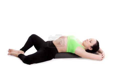 Photo pour Fille sportive sur le fond blanc se reposant dans la pose de yoga de l'angle de limite inclinante, Supta Baddha Konasana, réparateur, asana de détente, utilisant le soutien - image libre de droit