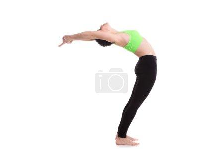 Photo for Sporty girl on white background doing exercises for flexible spine, Standing Backward Bend yoga posture, Ardha Chakrasana, Half Wheel pose, hands in vajra-mudra - Royalty Free Image