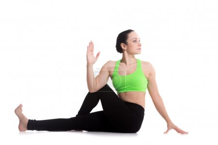Photo for Beautiful athletic girl practicing seated spinal twist, Half lord of the fishes pose, Ardha Matsyendrasana, yoga for back and hips - Royalty Free Image