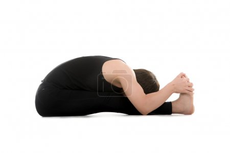 Foto de Athletic young man does yoga exercises, seated Forward Bend pose (Intense Dorsal Stretch), Paschimottanasana, stretching spine, shoulders, hamstrings - Imagen libre de derechos