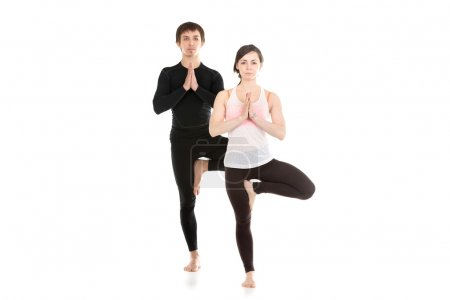 Photo for Two sporty people practice yoga in pair, couple doing exercise for spine, standing in Tree Pose, hands in Namaste, Anjali mudra - Royalty Free Image