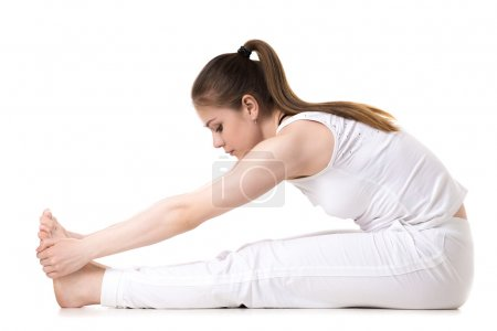 Photo for Young fitness model in white sportswear doing yoga or pilates training, seated Forward Bend pose (Intense Dorsal Stretch), Paschimottanasana, side view - Royalty Free Image