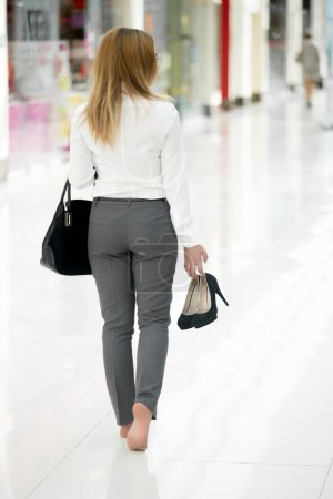 Young woman in office style clothes carrying in ha...