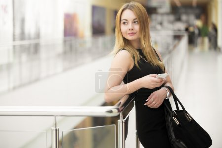 Attractive young woman with suede bag, wearing bla...