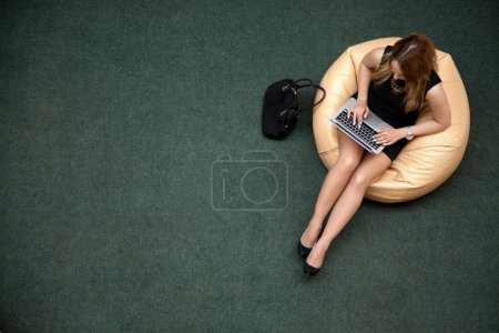 Foto de Young female sitting on bean bag working on laptop in public wifi area, typing, top view, copy space - Imagen libre de derechos