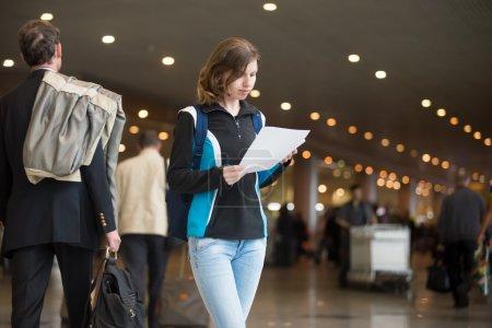 Photo pour Portrait de jeune femme dans la vingtaine avec sac à dos debout dans l'aérogare, avec des billets électroniques imprimés, en utilisant un téléphone portable pour s'enregistrer, foule floue de voyageurs sur le fond - image libre de droit