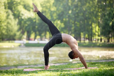 Photo for Profile of attractive sporty Indian young man working out on riverbank in park, doing Bridge exercise, backbend, One legged Upward Bow (Wheel) Pose, Eka Pada Urdhva Dhanurasana, full length - Royalty Free Image