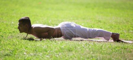 Chaturanga dandasana yoga pose in park