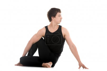 Photo for Sporty attractive young man working out, siting in Half lord of the fishes pose, Ardha Matsyendrasana, therapeutic for digestive organs, spinal cord and back, studio shot, full length - Royalty Free Image