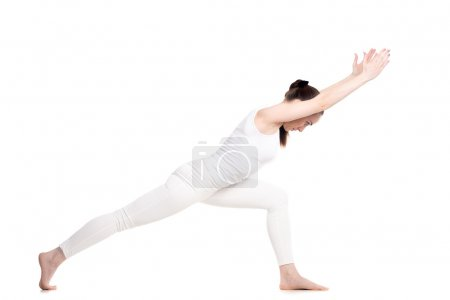 Photo for Sporty beautiful young woman in white sportswear doing lunge exercise, standing in Warrior I posture variation, Virabhadrasana 1, profile view, studio shot, isolated, full length - Royalty Free Image