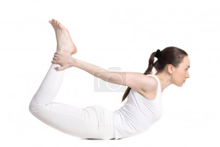 Photo for Sporty beautiful young woman in white sportswear doing backbend exercises, lying in dhanurasana, Bow Pose, studio full length side view, isolated - Royalty Free Image