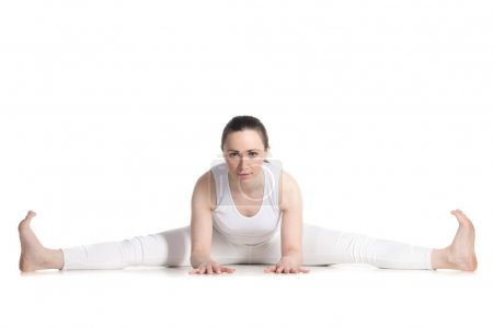 Photo for Sporty beautiful young woman in white sportswear sitting in Wide-Angle Seated Forward Bend pose, Upavishtha Konasana, dragonfly yin yoga posture, studio full length isolated shot, front view - Royalty Free Image