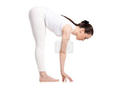 Yogi female standing in Uttanasana pose