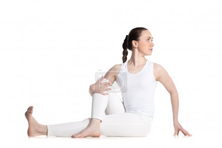 Photo for Sporty beautiful young woman in white sportswear sitting in Vakrasana, easy variation of Half lord of the fishes pose, Ardha Matsyendrasana, studio full length isolated shot, front view - Royalty Free Image