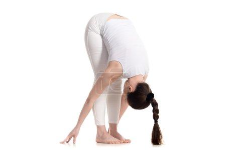 Foto de Deportiva hermosa mujer joven en ropa deportiva blanca con lindo peinado trenzado largo haciendo Standing Forward Bend, uttanasana pose, estudio de tres cuartos de vista, aislado, parte de la serie Surya Namaskar - Imagen libre de derechos