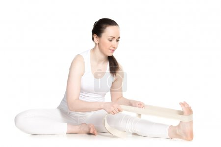 Foto de Sporty beautiful young beginning yoga student in white sportswear sitting in head to knee forward bend pose, doing Janu Sirsasana variation with strap, studio full length isolated shot - Imagen libre de derechos