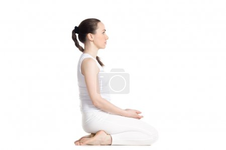 Photo for Sporty beautiful young woman practicing yoga, sitting on wooden block in seiza, vajrasana, thunderbolt or diamond asana for meditation, breath work, studio full length isolated shot, side view, white background - Royalty Free Image