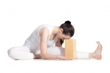 Photo for Sporty beautiful young beginning yoga student in white sportswear sitting in head to knee forward bend pose leaning on wooden block, doing Janu Sirsasana variation, studio full length isolated shot - Royalty Free Image