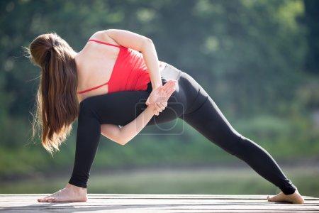 Teenage girl doing Revolved Side Angle Pose