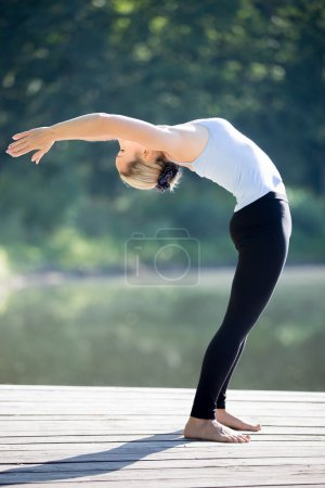 Photo for Beautiful sporty fit blond young woman in blue tank top sportswear working out outdoors on summer day, doing Standing Backward Bend yoga posture, Half Wheel pose, full length - Royalty Free Image