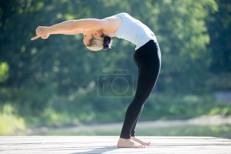Photo for Beautiful sporty fit blond young woman in blue tank top sportswear working out outdoors on summer day, doing Standing Backward Bend yoga posture, Ardha Chakrasana, full length - Royalty Free Image
