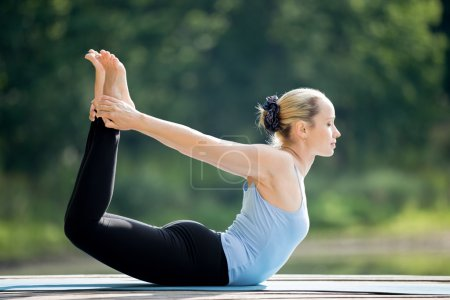 Photo for Beautiful sporty fit blond young woman wearing blue tank top sportswear working out outdoors on summer day, doing basic posture Dhanurasana, Bow Pose, full length - Royalty Free Image