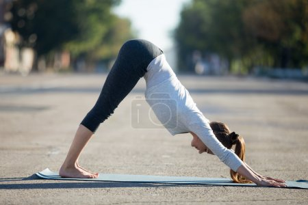 Photo for Yoga in the city: beautiful young sporty woman wearing sportswear working out on the street on summer day, doing downward facing dog posture, full length, profile view - Royalty Free Image
