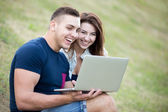 Couple using laptop on lawn