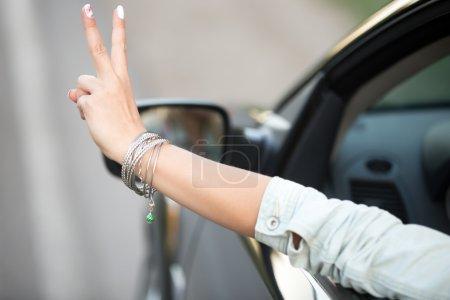 Photo pour Belle jeune femme en denim casual veste équitation voiture moderne, montrant le geste de la victoire à travers la fenêtre, bouchent de main avec bracelet fashion mignon, vue arrière - image libre de droit