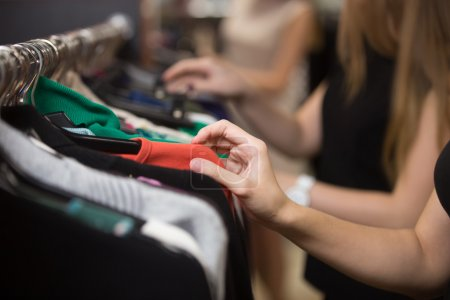 Woman choosing clothes on rack, closeup