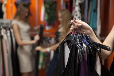 Photo for Close up of hands of young beautiful woman holding bunch of hangers with different dresses. Lady doing shopping, going to fitting room in fashion mall, carrying new casual style clothes - Royalty Free Image