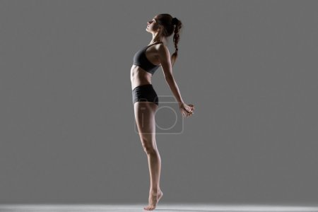 Photo for Portrait of beautiful young flexible fit woman in sportswear doing sport exercises for spine and shoulders, standing on tip toes, bending backwards, full length, side view, studio, gray background - Royalty Free Image