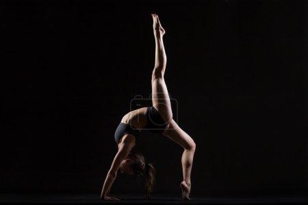Photo for Beautiful cool young fit woman in sportswear doing sport exercise, backbend, One-legged Upward Bow (Wheel) Posture, Eka Pada Urdhva Dhanurasana, full length, side view, studio shot, black background - Royalty Free Image