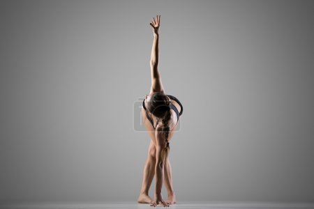 Photo for Portrait of beautiful young fit woman doing sport exercises for waist, shoulders and chest, warming up, full length, side view, studio shot on gray background - Royalty Free Image