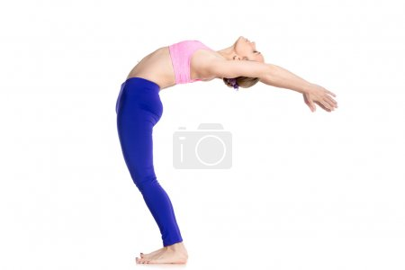 Photo for Sporty beautiful young blond woman in purple leggings doing Standing Backward Bend yoga posture, Half Wheel pose, studio full length isolated shot on white background, profile view - Royalty Free Image