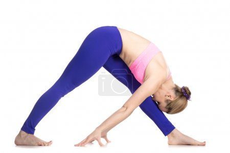 Photo for Sporty attractive young blond woman doing Pyramid Pose, Intense Side Stretch Posture, Parsvottanasana, studio full length isolated shot, profile view on white background - Royalty Free Image
