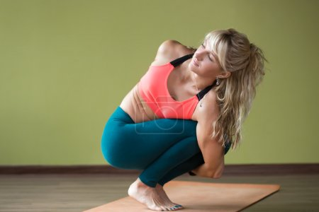 Photo for Sporty beautiful blond young woman in sportswear working out indoors, doing Noose Pose, Pasasana on orange eco mat, therapeutic for back, shoulder and neck tension, full length - Royalty Free Image