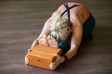 Paschimothanasana posture with Iyengar blocks