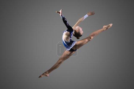Photo pour Belle jeune femme fraîche de gymnaste de forme dans la robe bleue de sportswear travaillant dehors, exécutant l'élément de gymnastique d'art, sautant, faisant le saut fendu dans l'air, dansant, pleine longueur, studio, fond foncé - image libre de droit